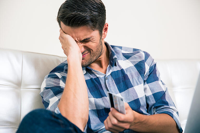 Portrait of a sad man holding bank card at home-1